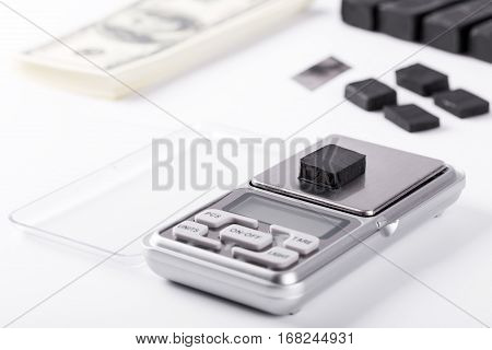 Blocks Of Hashish On Digital Scales Over White Background