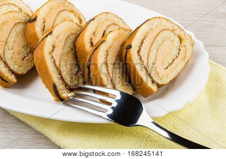 Swiss Roll Cake In White Dish On Yellow Towel