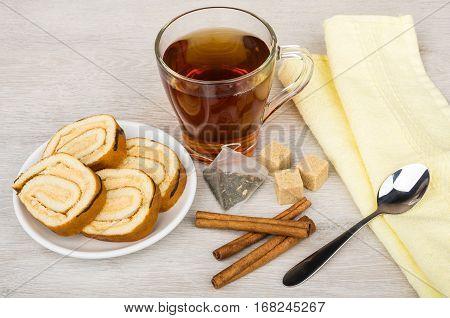 Swiss Roll Cake, Sugar, Tea Bag, Teacup And Cinnamon Sticks