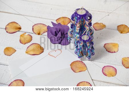 St. Valentine's Day: two violet carved candles, flower and petals of roses. Symbol.
