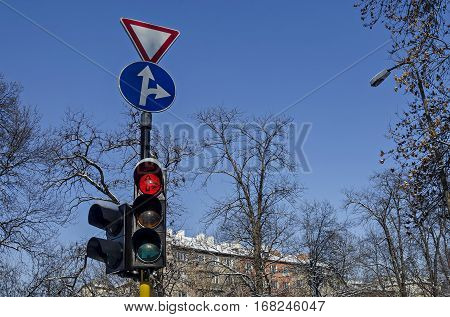Red color on the traffic light with beautiful blue sky, winter roof and tree branch in background, Sofia, Bulgaria