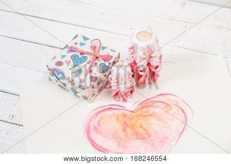 St. Valentine's Day: two carved candles of pink color, the packed gift and big heart. Gift.