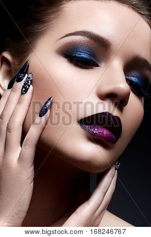 Young woman with creative make-up and violet lips with a gradient and sparkles on the face. Beautiful model with bright nails with rhinestones. The beauty of the face. The photo was taken in a studio.
