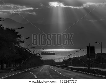 Beaming sunlight above the Red Sea, view from a street in Eilat, Israel. B&W filtered image for inspiration of retro style