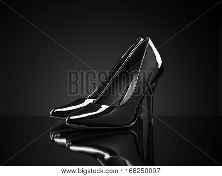 Black shiny stiletto heeled pumps on black reflective background.