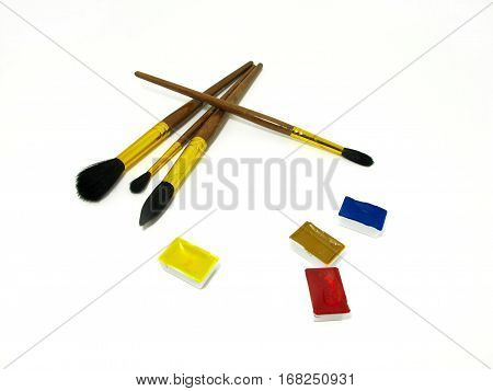 Brushes and watercolor couvettes on white background in a chaotic manner.