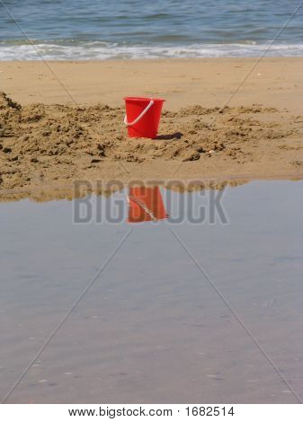 A Red Plastic Bucket On A Sandbank