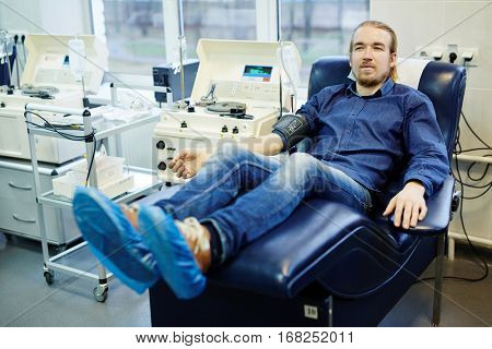 Donor of blood sitting in armchair by platelets blood separation machine