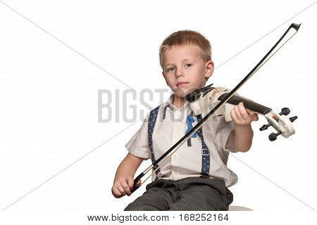 Little beautiful boy in shirt sitting in a chair, playing the electric violin, isolated on a white background