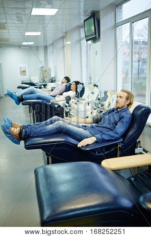 Row of young people donating their blood