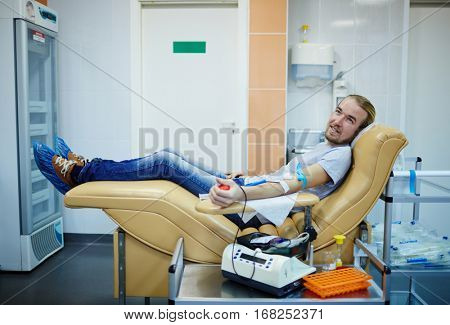 Young donor of blood sitting in armchair in hemotransfusion station