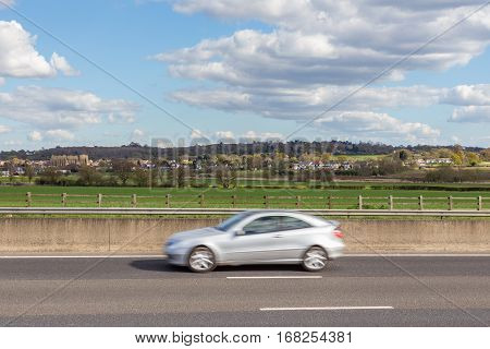Speeding car on the motorway with countryside and village in the background.