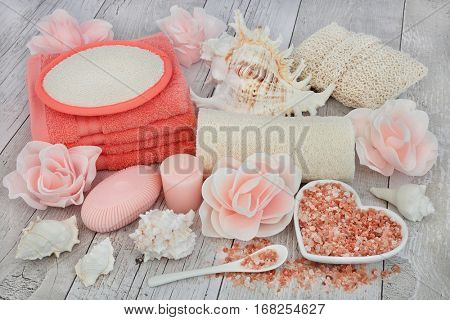 Cleansing spa accessories with himalayan salt, rose soap petals and exfoliating bathroom products on distressed white wood background.