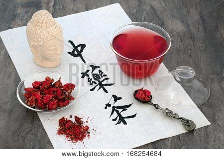Chinese pomegranate herb flower tea with calligraphy on rice paper, glass tea cup and old spoon, also used in alternative herbal medicine. Translation reads as chinese herb tea.