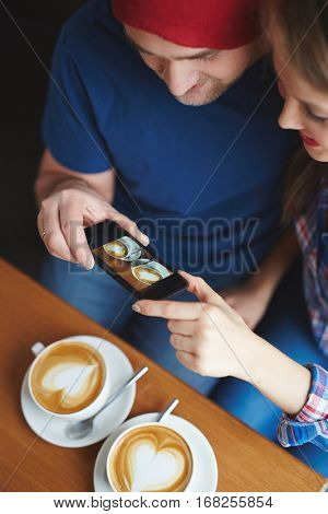 Happy young dates capturing their drinks in cafe