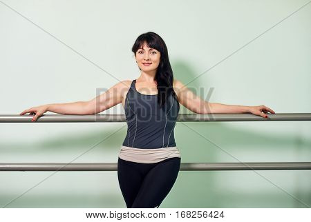 Portrait of middle-aged woman in a gym looking at camera in a fitness club