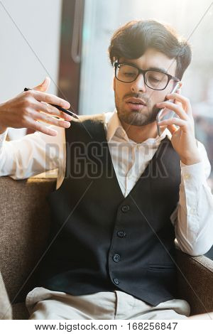 Portrait of concentrated dark-haired bearded chief in glasses and waistcoat discussing new company strategies on the phone and gesticulating while having coffee break in cafe.