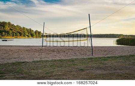 Beach Volleyball net on a beach with grass in front