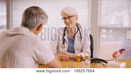 Friendly Woman Doctor Prescribing Medication To Elderly Patient