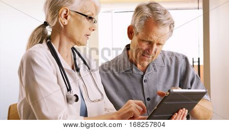 Woman Senior Doctor Expressing Health Concerns With Elderly Man Patient