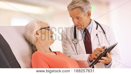 Confident Doctor Talking With Elderly Woman Patient In The Office