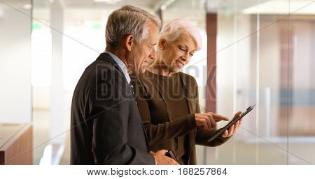 Senior Business Team Going Over Financial Data On Tablet In The Hallway