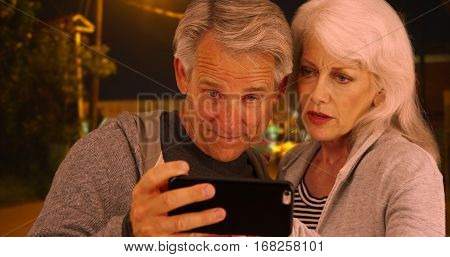 Confused elderly couple lost in a different country and uses smartphone for help