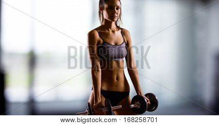 Young Caucasian woman standing and dramatically lifts weights