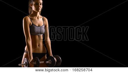 Young White Woman Lifts Weights On A Black Background With Copy Space
