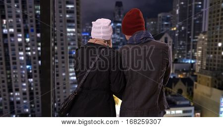 Yuccie couple enjoying the rooftop view together at night