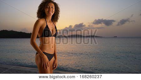 Young Black Woman Teasing In Bikini On Sun Setting Beach.