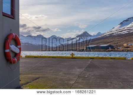 Lifebuoy and docks in the harbor of Stodvarfjordur on the East Icelandic coast looking out onto a beautiful mountain range scenery surrounding the fjord.