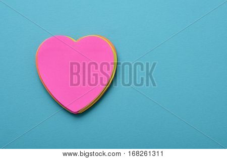 a stack of heart-shaped sticky notes of different colors topped by a pink one with a blank space in it on a blue background with a blank space at the right