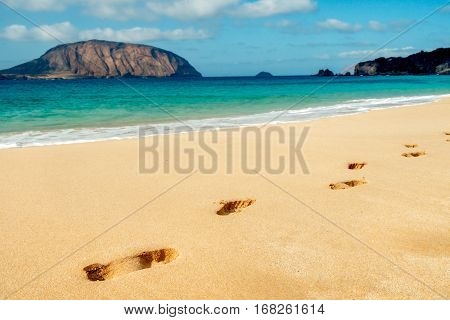 some footprints in the characteristic white sand of Playa de la Conchas beach in La Graciosa island, in the Canary Islands, Spain, with the Montana Clara Island to the left