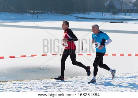OLDENZAAL NETHERLANDS - JANUARY 22 2017: Unknown senior athletes doing a cross run in a snow white landscape