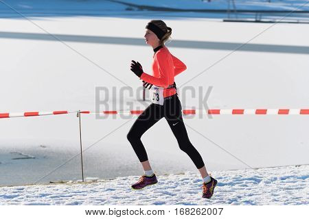 OLDENZAAL NETHERLANDS - JANUARY 22 2017: Unknown female athlete doing a cross run in a snow white landscape