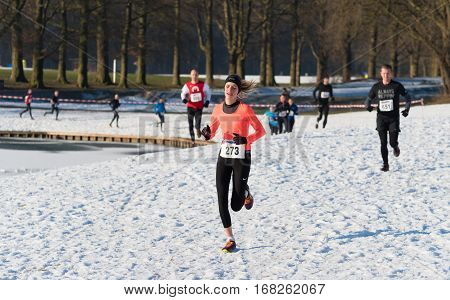 OLDENZAAL NETHERLANDS - JANUARY 22 2017: Unknown athletics doing a cross run in a snow white landscape