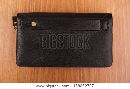 Men's black leather purse o on the wooden background