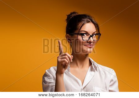Girl in glasses posing on a yellow background Gentle dreaming young girl thought woman Thoughtful girl The idea came in girl head The woman raised her index finger up.