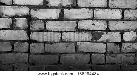 The texture of the brickwork. Roughly stacked bricks. Horizontal background. Black and white photo.
