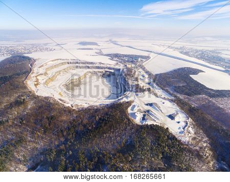 Aerial view to open cast mine. Industrial landscape in wintertime. Heavy industry with problems from cold weather and snow calamity.