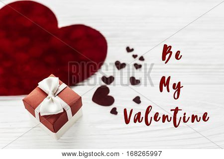 Be My Valentine Text Sign. Stylish Present Box And Velvet Hearts On White Wooden Background. Happy V