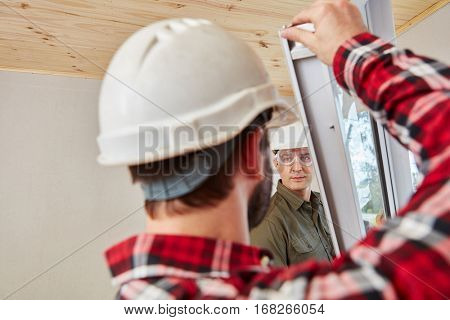 Window fitters mounting window with cooperation