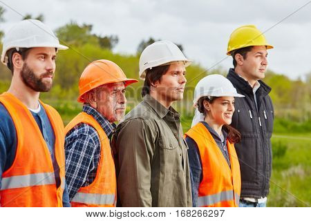 Craftsmen team of collegues as a group using protective clothes