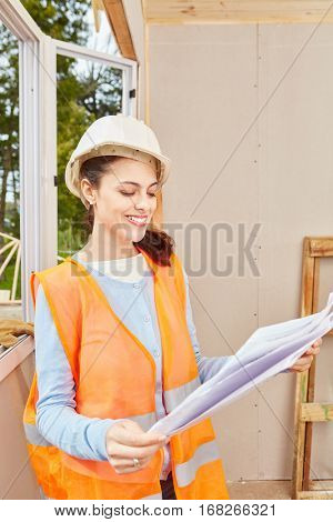 Woman as apprentice of craftsman holding architectural drawing
