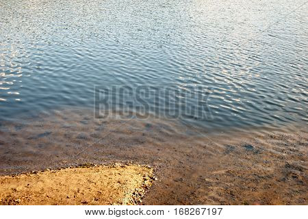 Sandy coast and ripple water with sky reflection, natural mirror, nature wonders, a lot of space for text