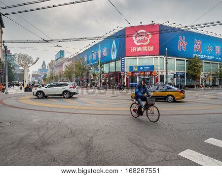 Beijing, China - Oct 30, 2016: Cars and bike traverse a major intersection at the 700-year-old Wangfujing Street and Dengshikou West Street. A popular shopping area for locals and visitors ahead.
