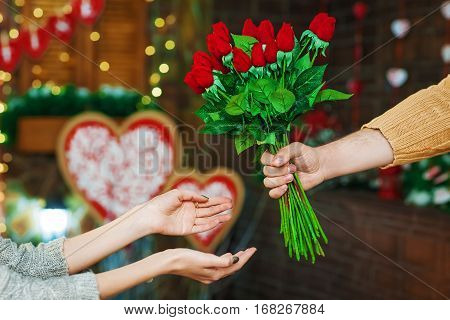 Close up shot of male hand holding a bouquet red roses. Only hands with flowers over valentines day decoration