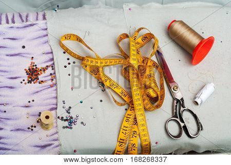 Sewing textile or cloth. Work table of a tailor. Textile tools. Scissors reel of thread measuring tapes and natural fabric. Copy space. Top view.