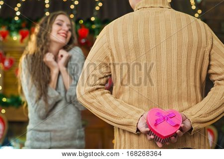 Man holding gift in hands behind his back, pink box with heart-shaped with purple bow. girl with impatient waiting gift